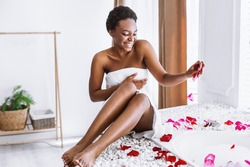 Relax in evening. Smiling african american girl in towel makes bath with foam and petals