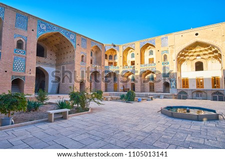 Relax in tiny garden of Ganjali Khan Caravanserai - historical building with preserved medieval architecture, masterpiece tilework and muqarnas (honeycomb) arches, Kerman, Iran. #1105013141