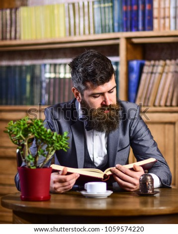 Relax, pleasure, leisure, hobby concept. Mature man with calm face has cup of tea. Businessman sits in vintage interior and enjoys relaxing reading. Bearded man in luxury suit in public library. #1059574220