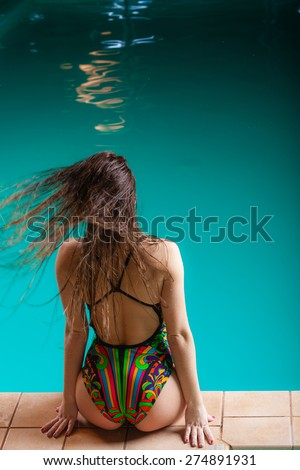 Relax, rest and recreation. Long haired woman back in colorful swimsuit on pool edge.