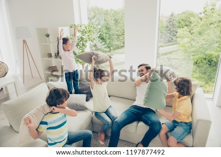 Relax, rest, chill lifestyle happiness pre-teen preteen concept. Best team ever! Portrait of handsome, attractive dad and four kids make pillow fight play on couch in light bright living room