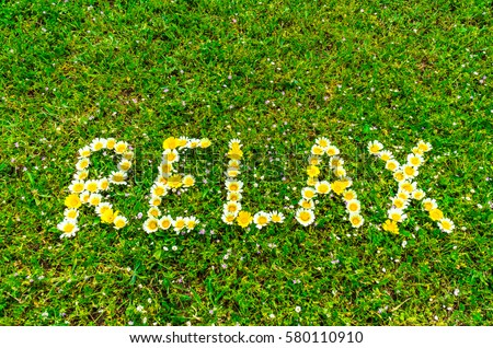 Relax text word written with flowers in green grass background, relaxation concept for spa or health. #580110910