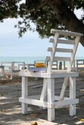 Relax time on the beach sit on the white chair with music speaker and pocket book concept for tourism
