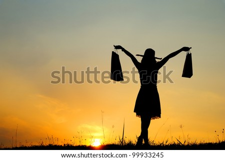 Relax Woman holding shopping bags in sunset silhouette