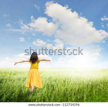 Relax Woman in green grass fields with clouds sky