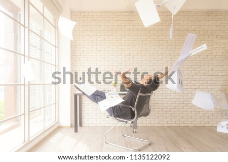 Relax working.  Asian businessman tossing a bunch of papers celebrating the end of his work and success report. He relax and happy with your work. Business Concept