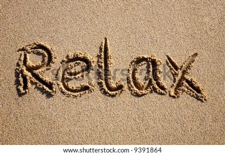 Relax, written on a sandy beach.