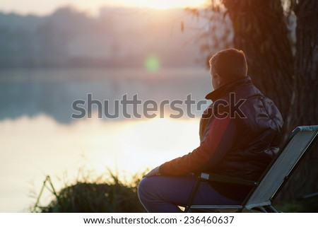Relax /  Young boy watching the sunset near the lake - Shutterstock ID 236460637