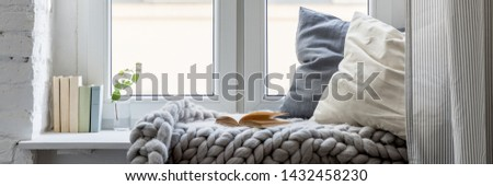 Relaxation area with books, pillows and cozy blanket on a wooden windowsill, panorama