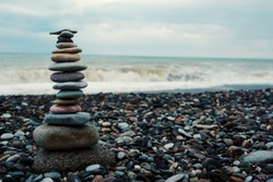relaxation at sea. Stack of stones on beach. Stone cairn on natural background - blurred sea and sky. Concept balance