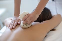 Relaxation. Dark-haired woman having bags ayurvedic massage in salon