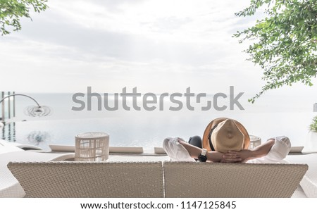 Relaxation holiday vacation of businessman take it easy happily resting on beach chair at swimming pool poolside beachfront resort hotel peacefully with sea or ocean view and summer sunny sky outdoor