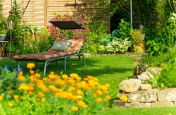 Relaxation in the landscape garden. Garden furniture. lounger on green grass in backyard. Comfortable chair sun lounger for sunbathing outdoors