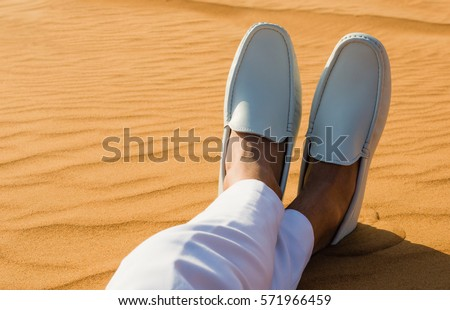 Relaxation. Mans legs/feet lying on the hot desert sand.