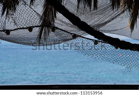 Relaxation on the beach: morning sea with palm tree silhouettes and fishing nets	 Relaxation on the beach: morning sea with palm tree silhouettes and fishing nets