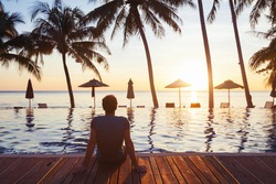 relaxation on the beach, young man enjoying beautiful sunset in luxury hotel near swimming pool