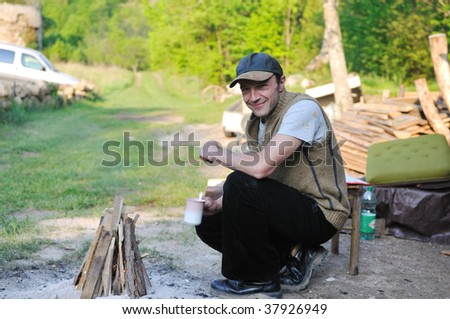 relaxed adult man drink fresh coffee over fire