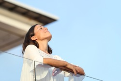 Relaxed adult woman breathing fresh air standing on a hotel balcony at summer