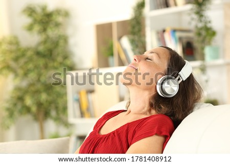 Relaxed adult woman listens to music with headphones in the coach at home