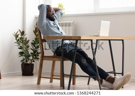Relaxed african american business man chilling in office room finished job well done, black male employee take break rest at desk holding hands behind head feel no stress free relief in work space