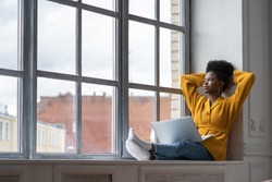 Relaxed African American millennial woman with afro hairstyle wear yellow cardigan, sitting on windowsill, resting, taking break from work on laptop, thinking and looking at window, hands behind head.