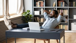 Relaxed african American young male sit at desk distracted from computer work take break daydreaming, calm biracial man lean in chair relax rest at office desk, breathe fresh air, stress free concept