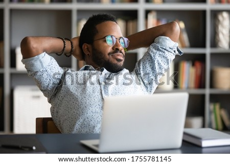 Relaxed african businessman stretch in office chair hands over head take break from work look at window feels satisfied by finished work project. Planning future opportunities, business vision concept Сток-фото ©