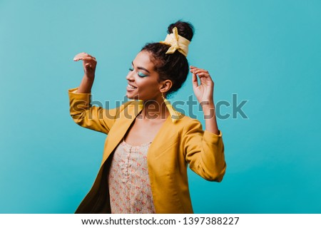 Relaxed african girl with bright makeup dancing with eyes closed. Indoor shot of blithesome black young woman chilling in studio.