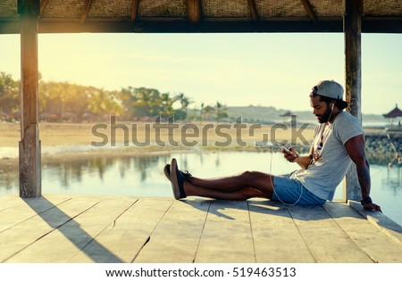 Relaxed and cheerful. Listening to music. Outdoor portrait of happy young african man resting on deck near the sea.