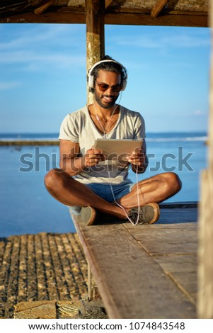Relaxed and cheerful. Work and vacation. Outdoor portrait of happy young african man using tablet computer on deck near the sea. #1074843548