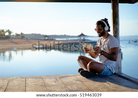 Relaxed and cheerful. Work and vacation. Outdoor portrait of happy young african man using tablet computer on deck near the sea. #519463039