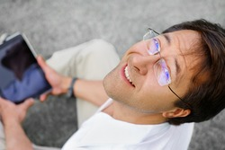Relaxed and positive man is surfing on his tablet