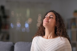 Relaxed arab woman breathing fresh air sitting on a couch in the living room in the night at home