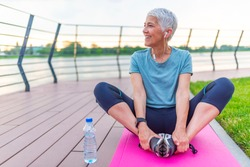 Relaxed athletic mature woman sitting on fitness mat outdoors. Senior Woman Resting After Exercises. Woman on a yoga mat to relax outdoor. Senior lady prefers healthy lifestyle