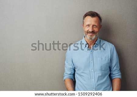 Relaxed attractive smiling middle-aged man with rolled up sleeves posing against a grey studio background with copy space