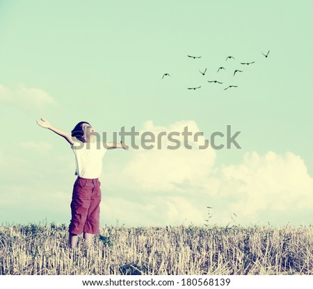 Relaxed boy breathing fresh air on a meadow with birds flying in background sky - stock photo
