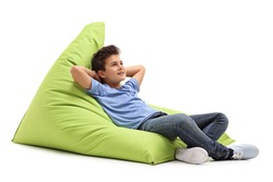 Relaxed boy laying on a comfortable green beanbag isolated on white background