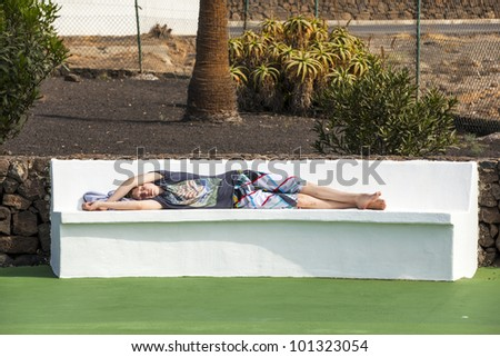 relaxed boy sleeping on the bench in the pool area