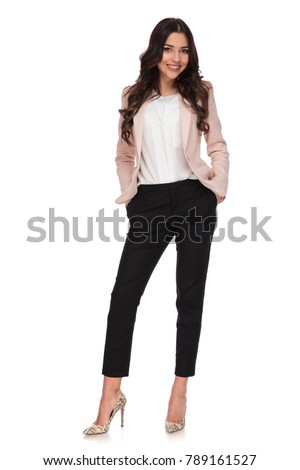 relaxed business woman standing with hands in her pockets on white background
