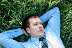Relaxed businessman in a meadow. Welldressed young business man is resting in a green grass  field. top view.