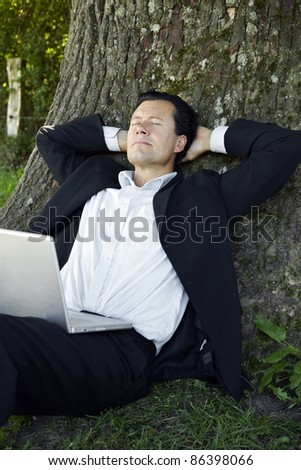 Relaxed businessman leaning on tree