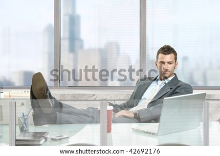 Relaxed businessman  sitting at desk in front of office windows, looking at laptop screen.