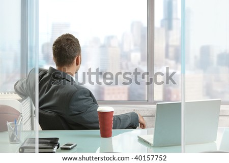 Relaxed businessman sitting at desk in office, looking out the windows to downtown skyscrapers.