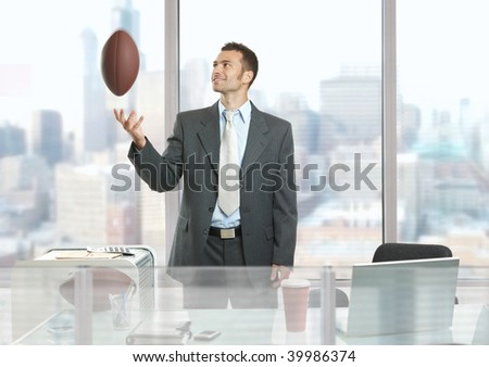 Relaxed businessman standing in front of office windows, playing with football and smiling.