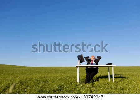 Relaxed businessman with hands behind head at desk on field