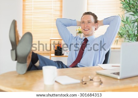 Relaxed businessman with his feet up in his office #301684313