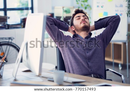 Relaxed businessman working  on computer