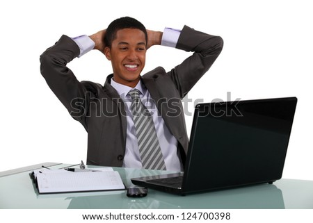Relaxed businessmen smiling at his laptop - stock photo