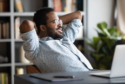 Relaxed calm young african businessman resting looking away sit at desk with laptop hands behind head, satisfied office employee take break feel stress relief peace of mind concept chill at work