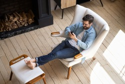 Relaxed casual guy lounge sit on comfortable armchair in modern house room with wooden floor fireplace using smartphone apps, happy young man hold cell phone play mobile games at cozy home, top view